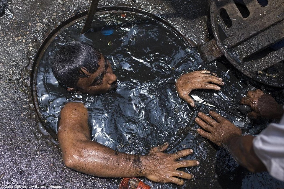 Meet man with worst job in the world! Sewer cleaner dives into filth to claw out blockages with his BARE HANDS (photos)