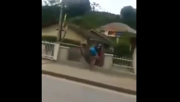 Two guys try to do a trick while riding the motorcyle but ends up in an accident
