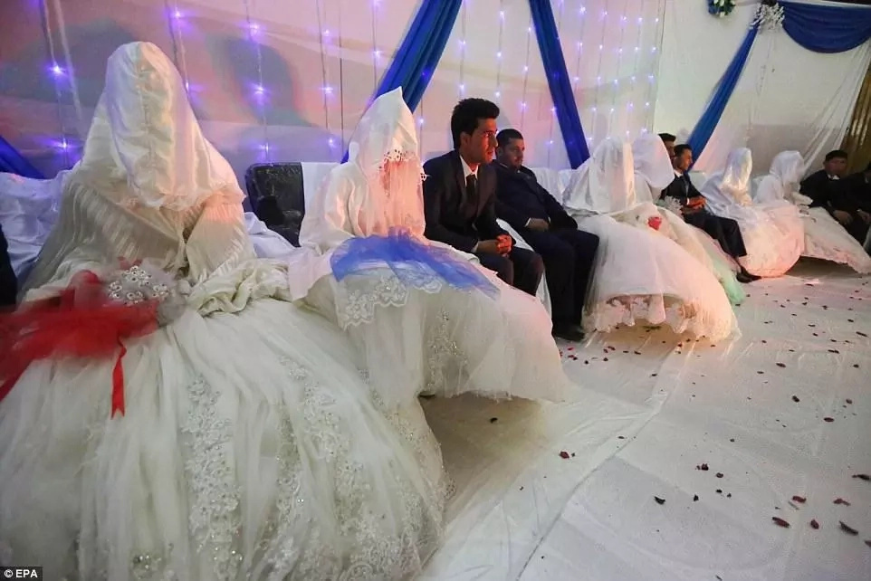 The brides, seen here sitting next to their grooms, were hooded