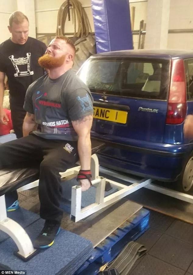 Greg Bramwell lifts a car. Photo: MEN Media