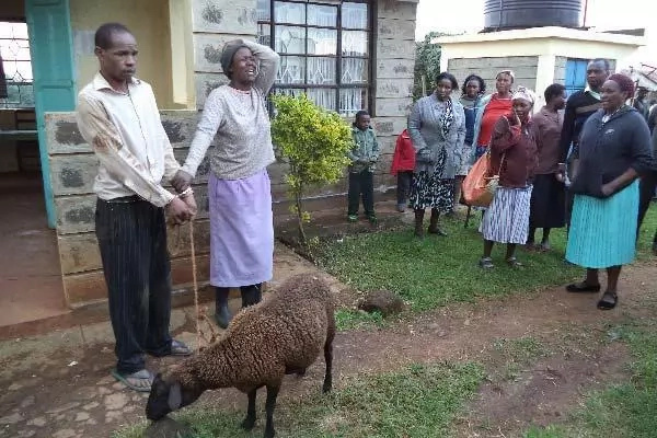Christopher Momanyi holding the sheep he was accused  to have committed bestiality with. His sister Mercy Kwamboka cries pleading with residents to let him go. PHOTO: The Star