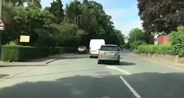 2 Enraged drivers in a road range race in a school street. Reckless driving caught by a motorist's dash cam.