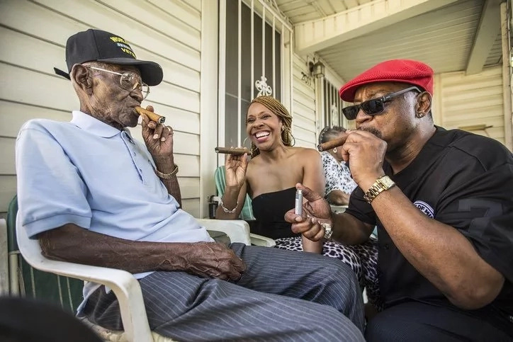 His friends in his neighborhood often join him to smoke cigars