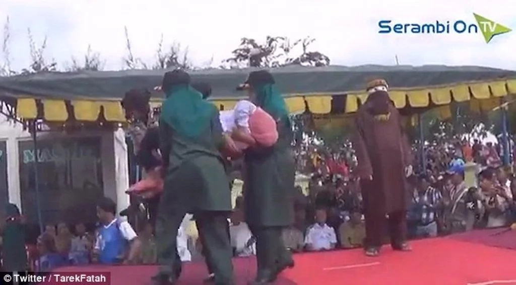 Woman collapses in agony after being lashed with cane in front of cheering crowd (photos, video)