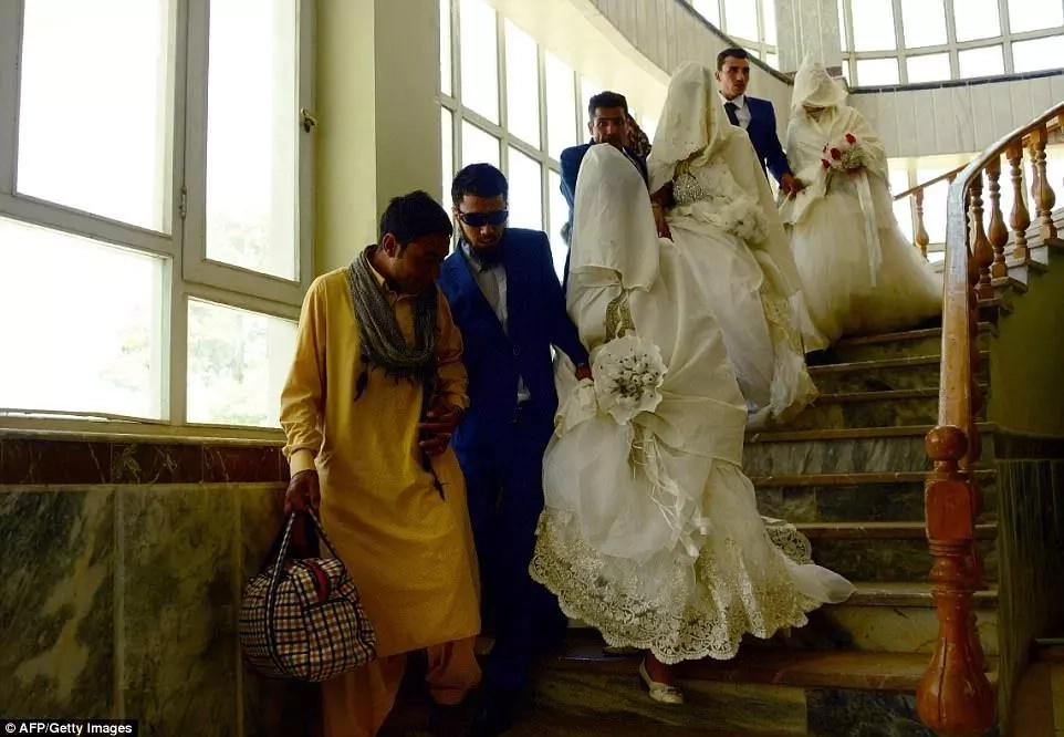 A blind groom is led down the stairs with his bride
