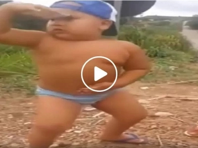 Energetic young boy hilariously shows off dancing prowess by the street