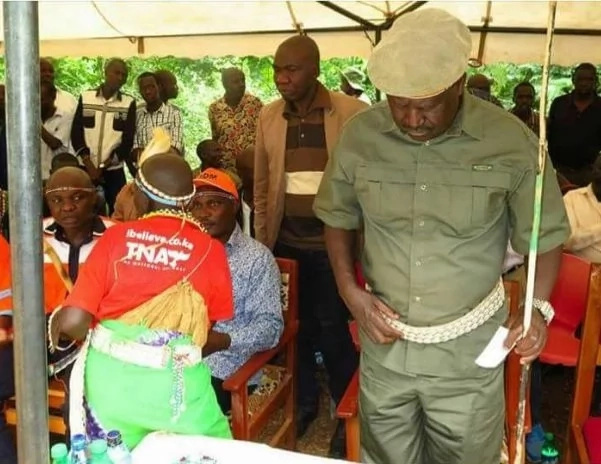 Woman stands near Raila in Jubilee T-shirt