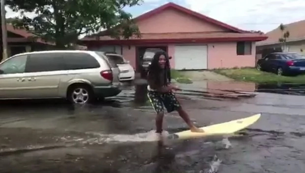 Man gets on his surfboard on flooded street