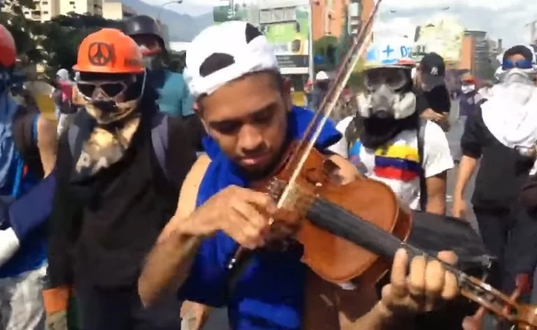 Music as rebellion! This young man plays his violin while teargas and bullets are thrown by police in riots (photos, video)
