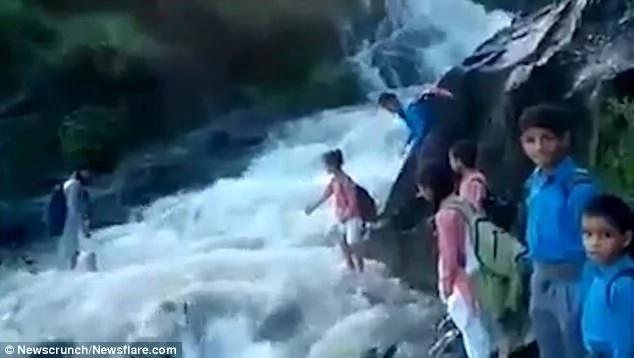 Heartening! Children risk to cross dangerous raging river just to get to school