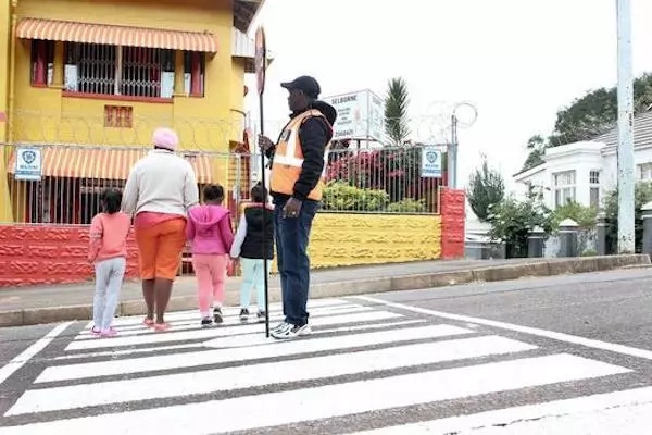 A security guard at the school helps children cross the street over the crossing McMullen painted. Photo: Se-Anne Rall