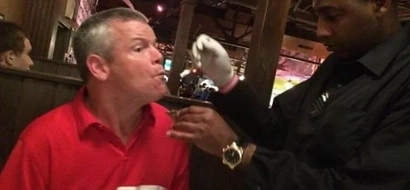 Man with cerebral palsy has trouble eating. Waiter voluntarily feeds him without hesitation