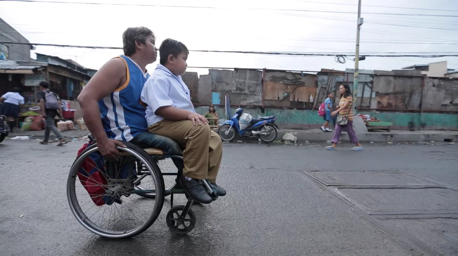 Wheelchair-bound father takes son to school in his wheelchair every day, rain or shine, earns praises and sympathy from netizens