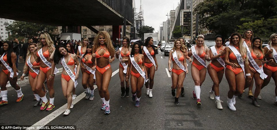 Female beauty pageant contestants race street with bare bottoms