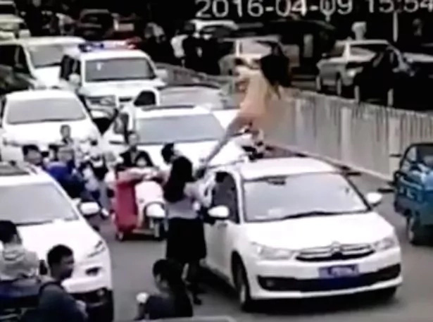 Nude woman dancing on car roof causes traffic jam in China