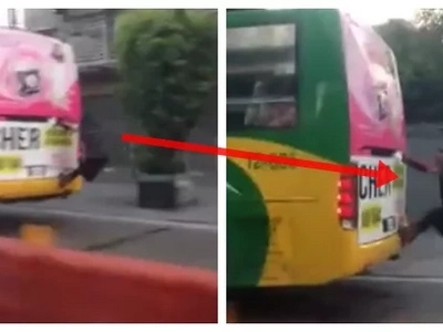 Kapit lang! Man latches on the back of a bus along EDSA