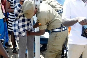 Photos: Uganda police strangely search fans private parts as they enter national stadium