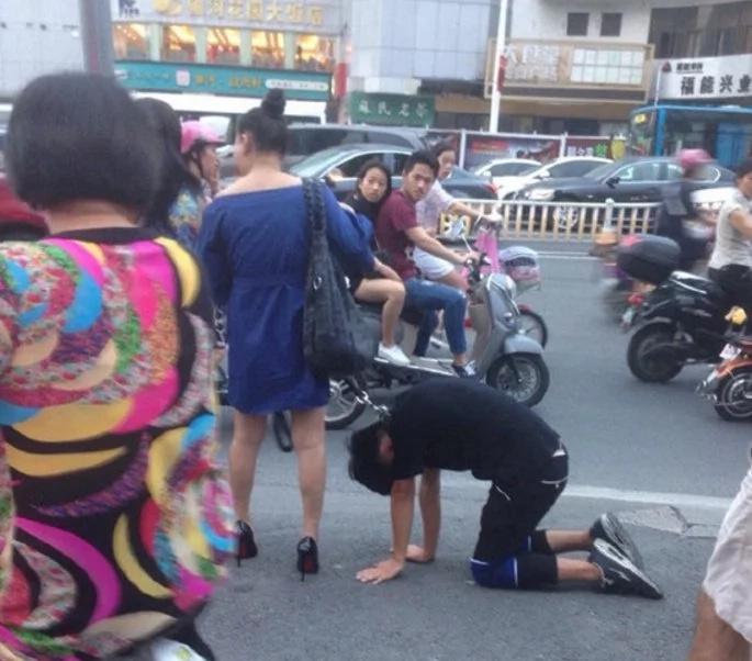 Shocking moment Chinese woman takes her man for a walk on a dog leash