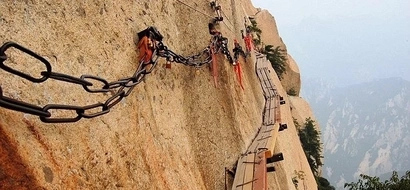 The world's scariest trail: Chinese tourists walk on narrow wooden plank 7,000 feet above the ground