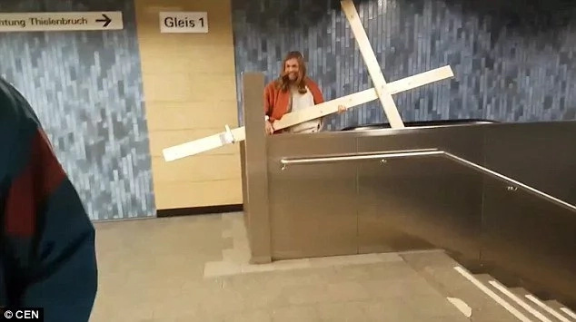 Funny moment as man dressed as Jesus gets his cross STUCK in the ceiling (photos, video)