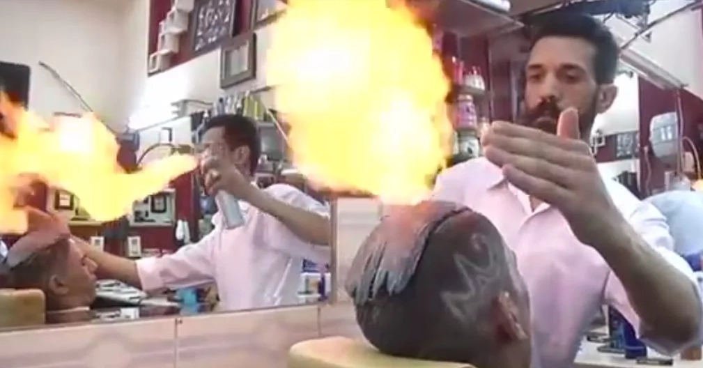 This African barber who uses fire to cut and style his clients' hair