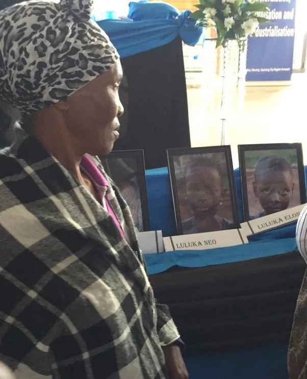 A parent looks at pictures of the pupils who lost their lives in the accident