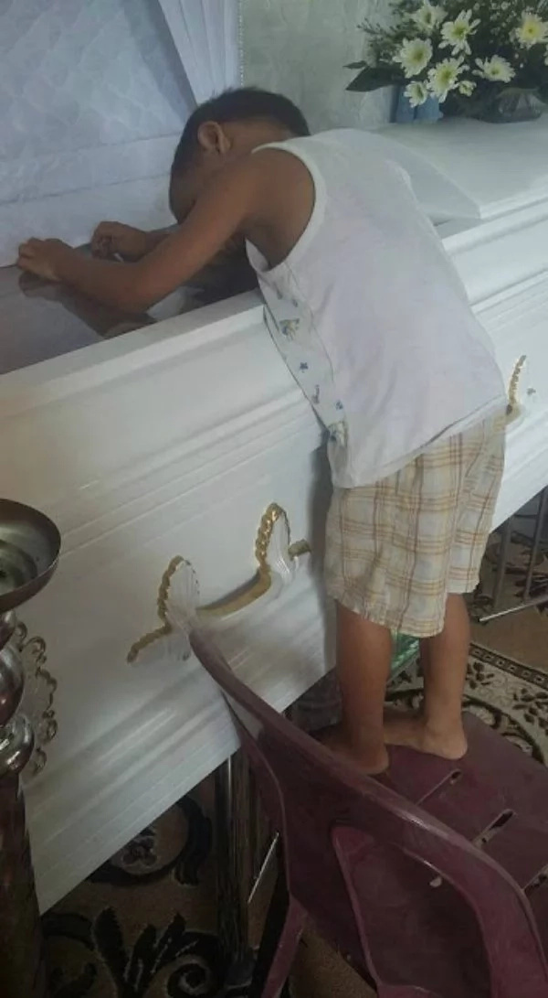 Touching photo of child hugging coffin of mom