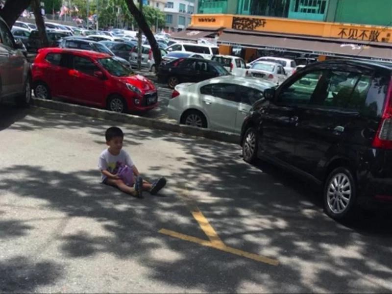 Obligó a su hijo a sentarse en el pavimento caliente para reservar estacionamiento