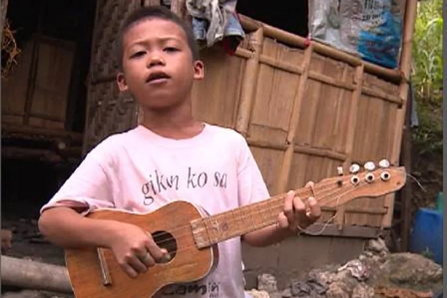 8-year old boy serenades people in exchange for money to feed sister