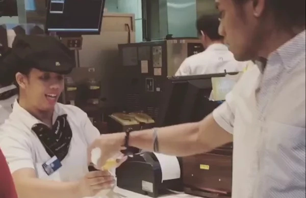 Customer surprises employee with grabbing ice cream by the hand