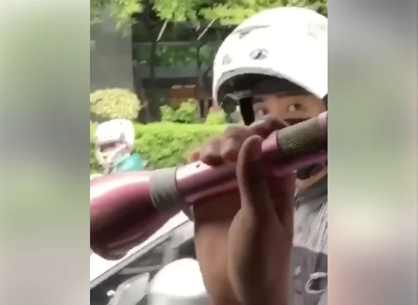 Filipino entertains by singing to the public inside a car while traffic