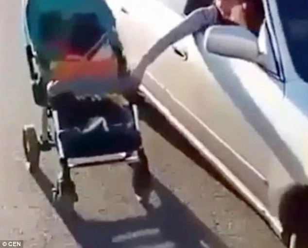 Reckless mother pushing her son in a baby buggy while driving