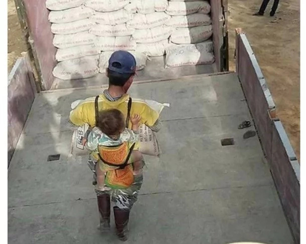 Dedicated father backpacking his son in a carrier while he worked