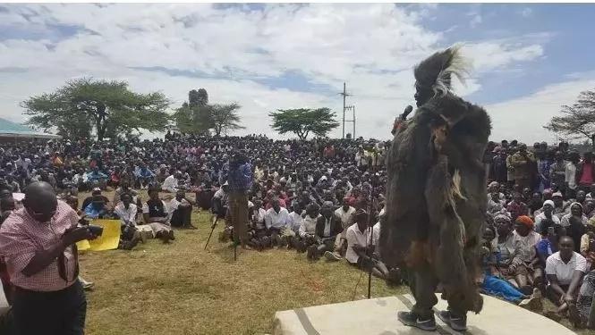 Woman stands near Raila in Jubilee T-shirt