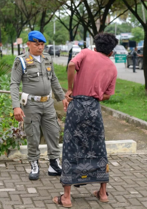 A police officer instructs a man to wear a sarong to cover his shorts. Photo: Getty