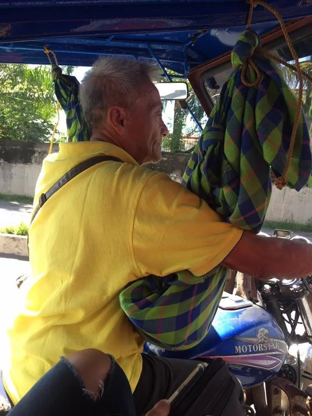 Father cradles toddler while working as tricycle driver