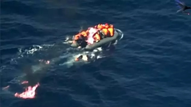 Dramatic footage shows the boat bursting into flames with the migrants onboard