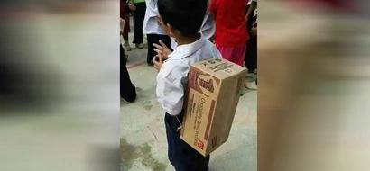 Mientras que muchos niños quieren bolsos costosos, este niño lleva sus útiles al colegio en una vieja caja de cartón