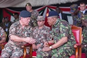 A  Photo of a highly trained Jordanian commando kneeling before Uhuru Kenyatta