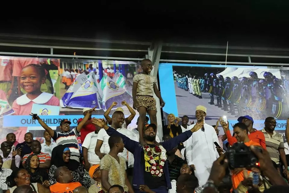 Photo of Joho carrying this boy like an acrobat carries the day