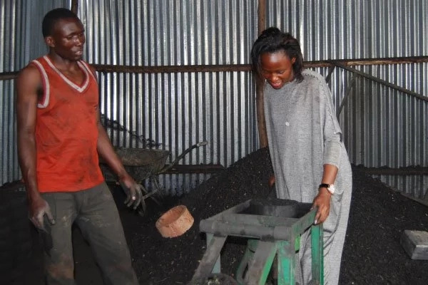 Catherine Nakitande demonstrates how to make a briquette. Photo: Daily Monitor