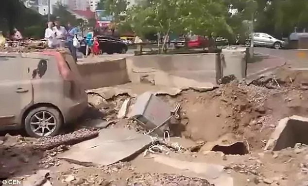 Confusion as underground water pipe EXPLODES, leaving behind 64ft hole and catastrophic damage (photos)
