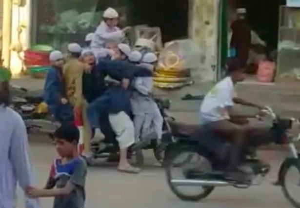 Passersby stare in shock as 11 passengers balance themselves at back of speeding motorbike