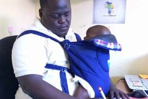 Kisumu man becomes the envy of women after carrying baby to work (photos)