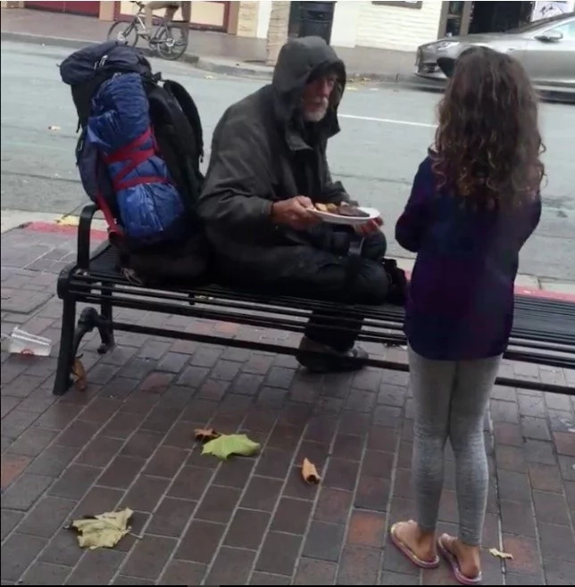 Adorable young girl shares her dinner with homeless man outside restaurant
