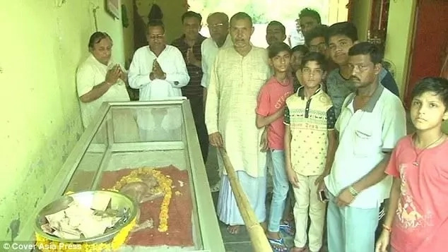 Villagers pose next to the dead calf