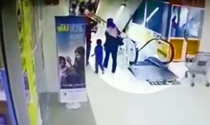 Little Girl Riding On Dad's Shoulders Falls Over The Side Of An Escalator
