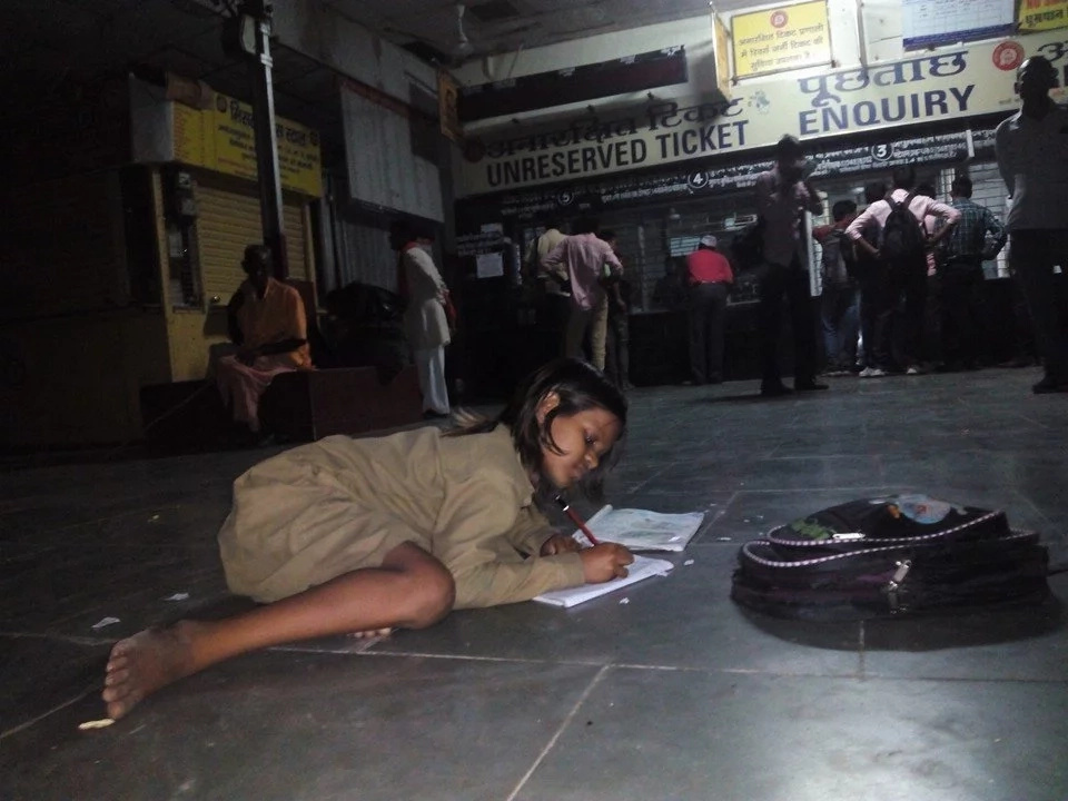 Selfless young girl studying at the railway station every day