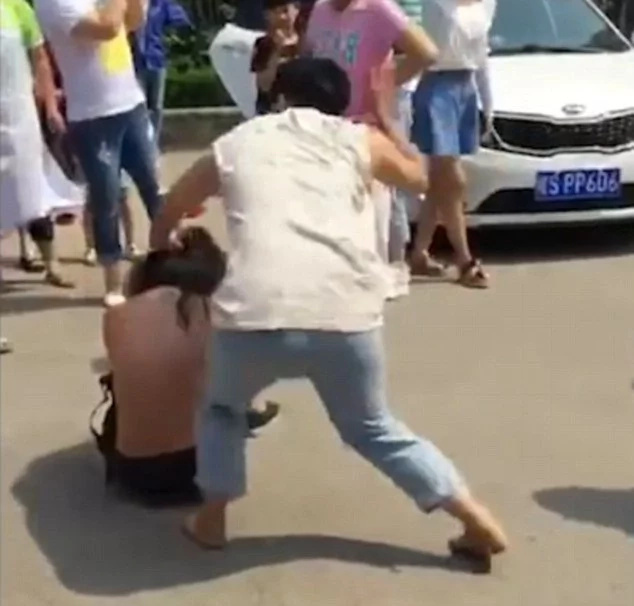Angry woman beats, strips husband's mistress in public