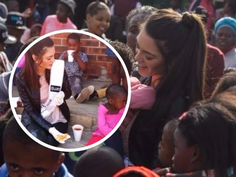 Beauty queen finds herself in hot soup for feeding black kids while wearing gloves